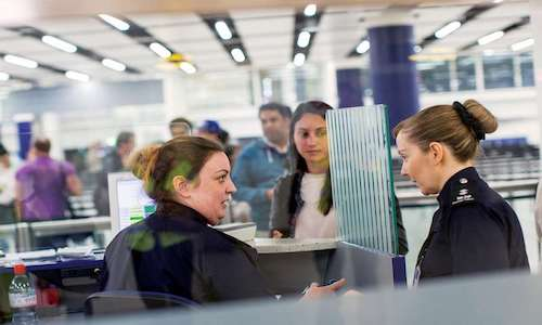 Border guards talking in an airport.